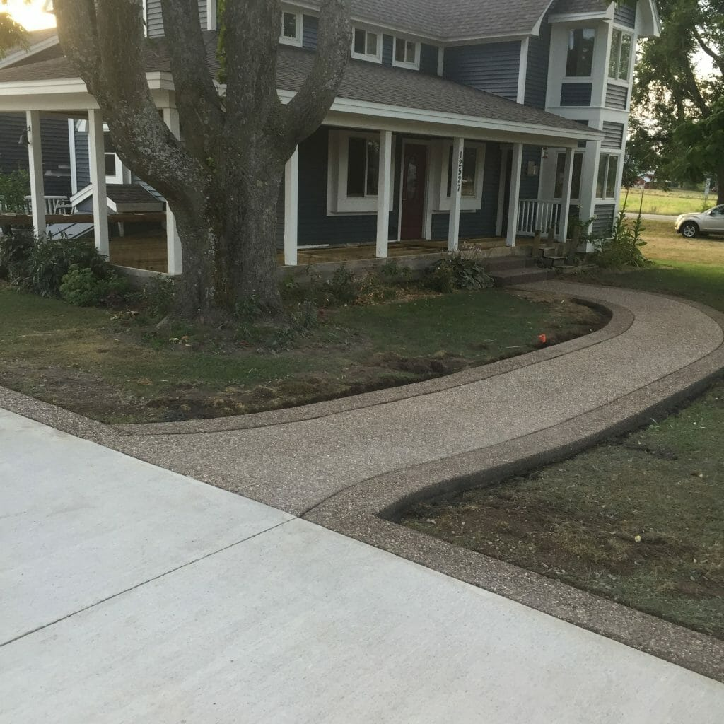 concrete walkway leading to blue house with white trim