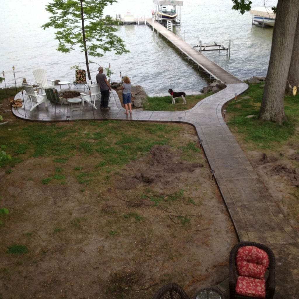 concrete sidewalk with fire pit and dock