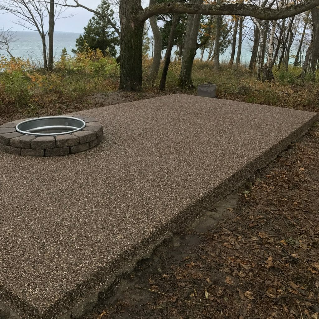 concrete patio with fire pit and trees in background