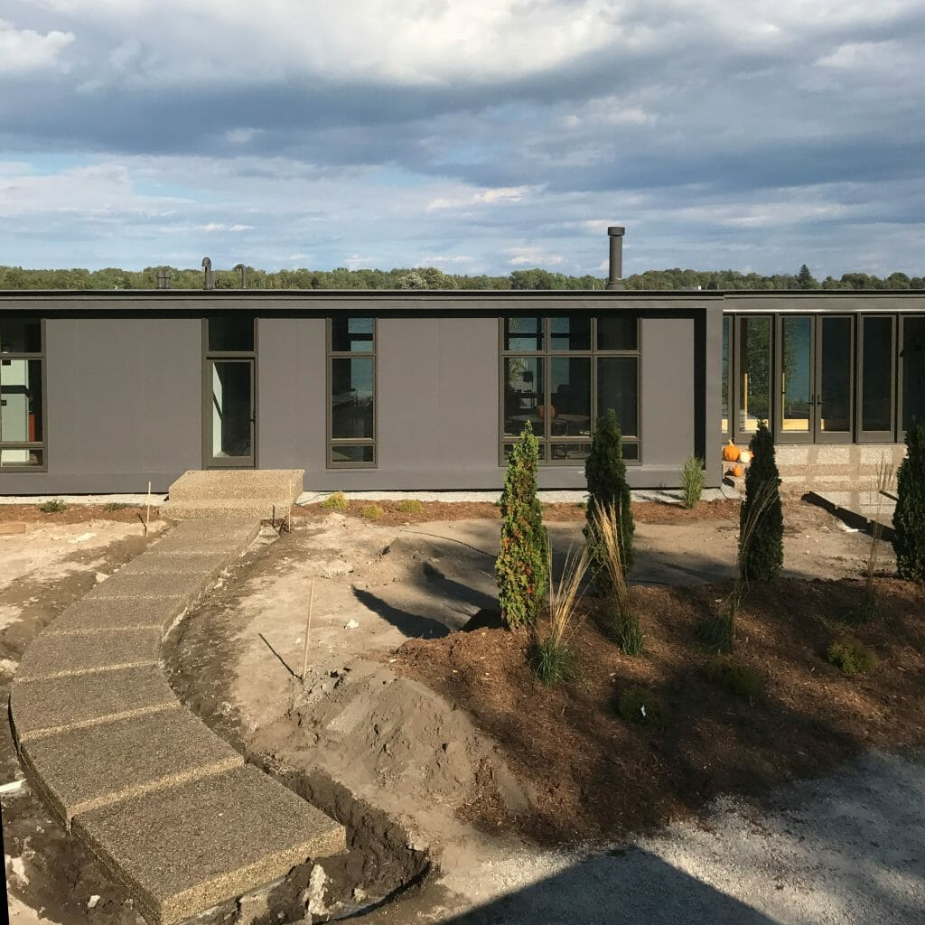 gray house with unfinished yard and new concrete side walk