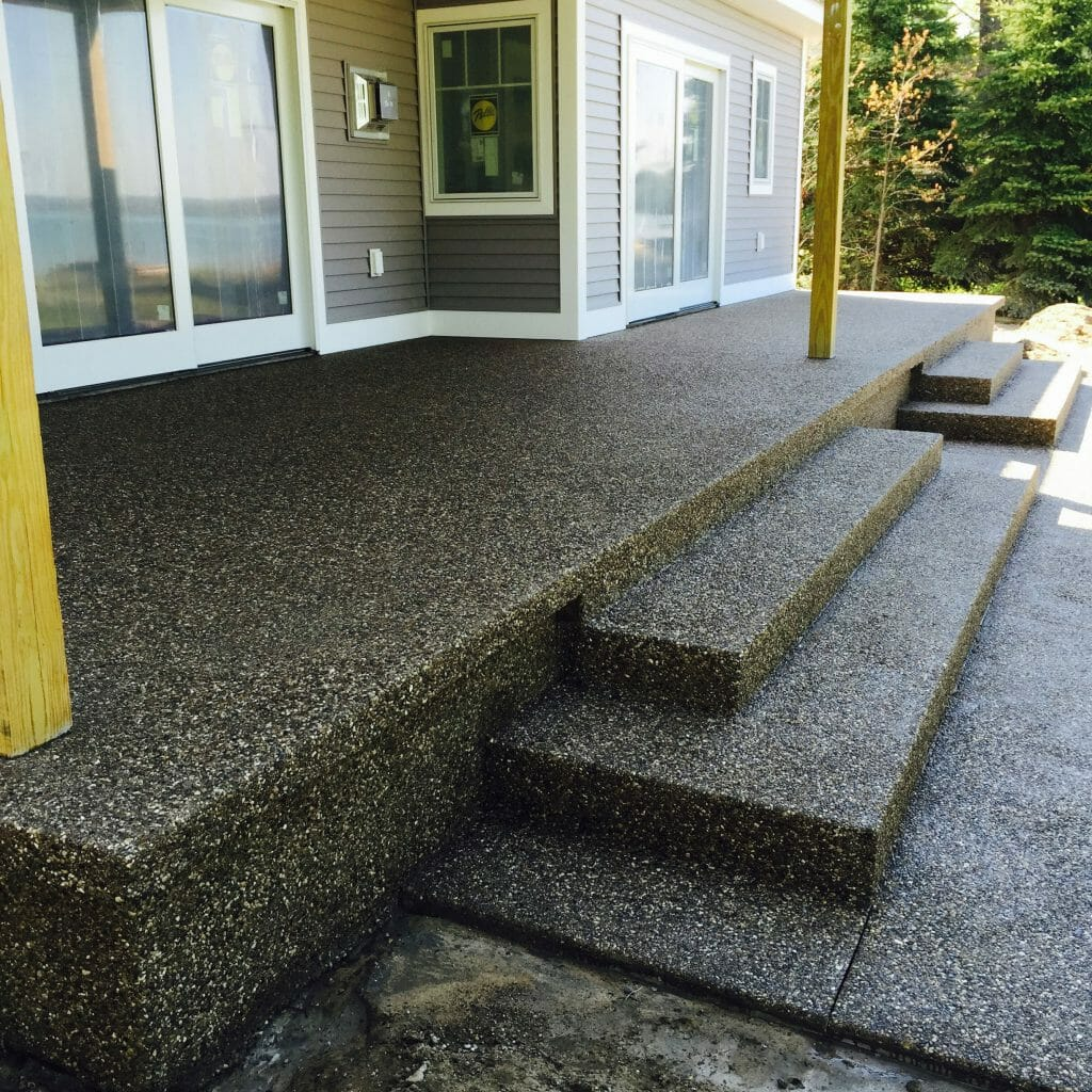 gray house with concrete patio and stairs