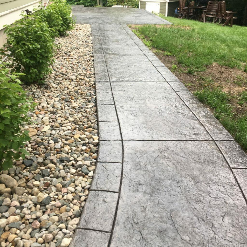 custom concrete sidewalk with plants and yard chairs