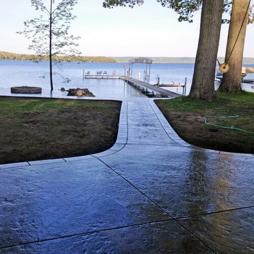 concrete path with fire pit and dock